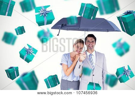 Business people holding a black umbrella against blue and silver presents