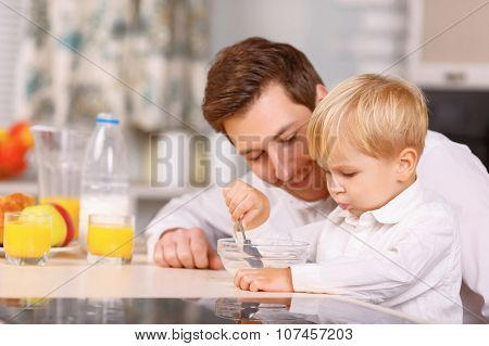 Daddy encourages his son to finish a cereal.