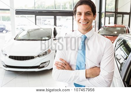 Smiling businessman standing with arms crossed at new car showroom