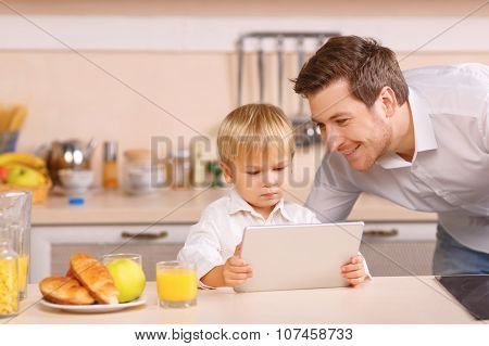 Little boy is playing with digital tablet.
