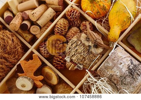 Autumn decoration accessories in wooden compartment for creative artwork.