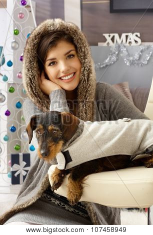 Xmas portrait of happy woman with her dackel in dog suit.