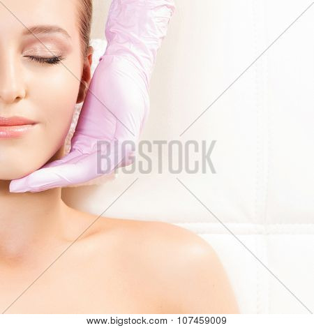Portrait of beautiful woman and the healer hands in gloves. Head massage treatment