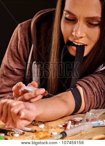 Female drug addict with  black tourniquet on his arm and  syringe.
