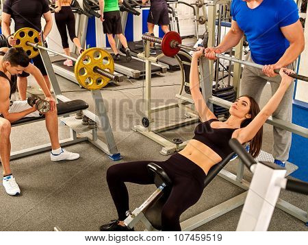Woman working his arms and chest at gym. She lifting barbell. Man help her.