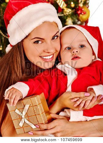 Mom wearing Santa hat holding  baby boy with gift box  under Christmas tree.