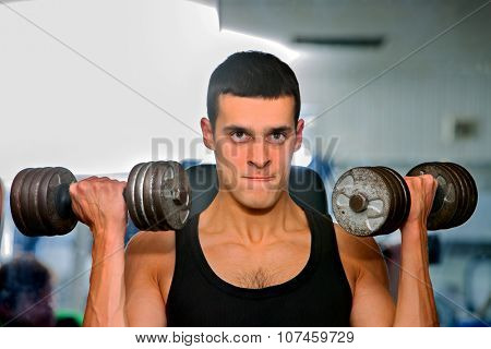 Man working his arms with very big dumbbells at gym. He lifting dumbbells.