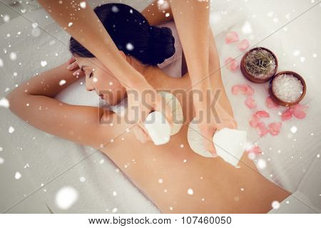 Snow against pretty woman enjoying a herbal compress massage