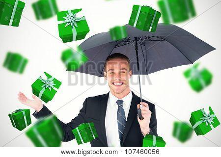 Businessman sheltering under black umbrella against green presents