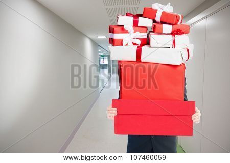 Businessman holding something with his hands against college hallway