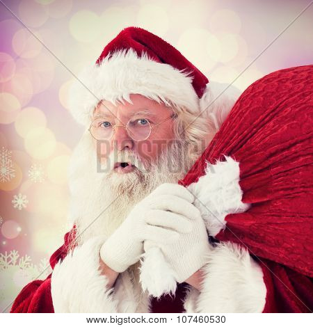 Santa takes care about his sack against glowing christmas background