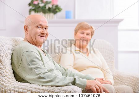 Loving adult couple sitting in arm chairs