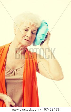 An old lady with ice bag by her head