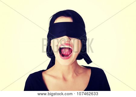 Portrait of a beautiful frighten young blindfold woman screaming