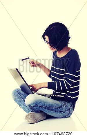 Woman with a laptop and a credit card, sitting on the floor.