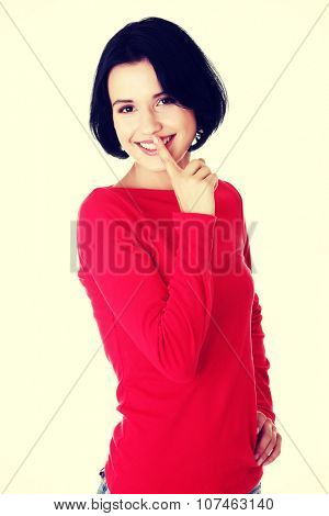 Happy woman making a keep it quiet gesture.