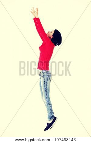 Teen girl jumping in air trying to catch something
