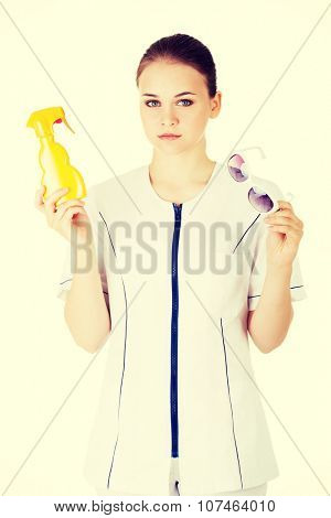 Young female doctor or nurse showing sunscreen and sun glasses fot sun uv protection.