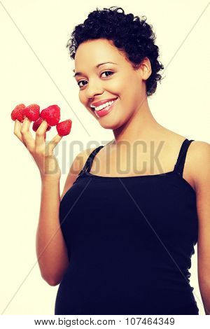 Young happy pregnant afro american woman with strawberries