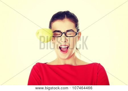 Casual woman in glasses hit by apple.