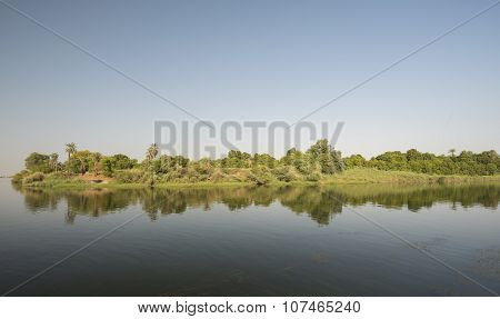 Bank Of A Large River With Reflection