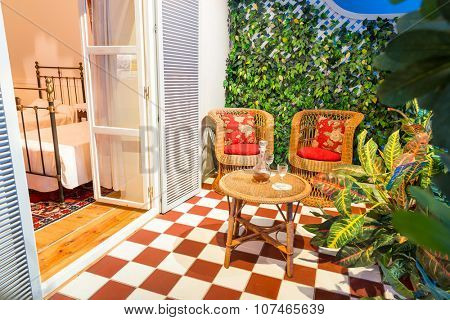 Cosy balcony with cane furniture and glasses of vine in the hotel room
