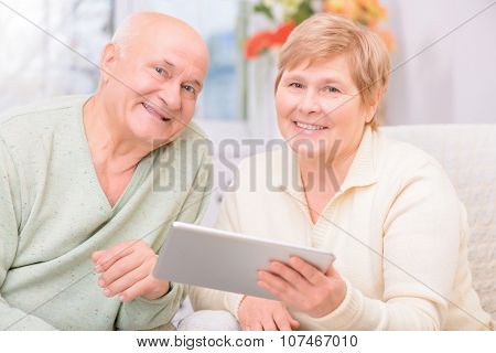 Adult couple holding laptop
