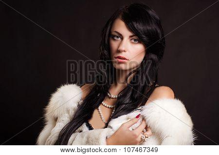 Beautiful girl with dark hair in a white fur coat