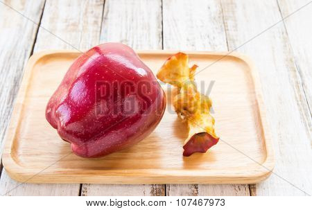 Red Apple And Apple Core In Wooden Plate On A White Wooden Background