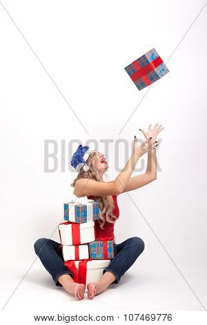 A Sexy Blonde With Big Breasts Sitting On White Background Among The Gifts In A New Year's Cap Blue