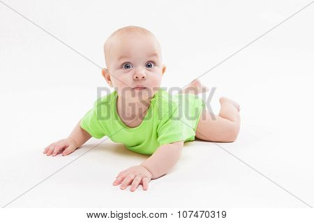 Cute Curious Baby Lies On Her Stomach And Looking At The Camera