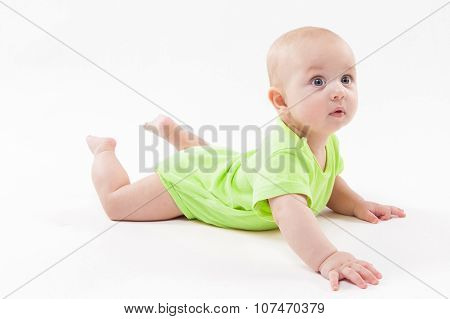 Surprised Cute Baby Lying On His Stomach And Looking At The Camera