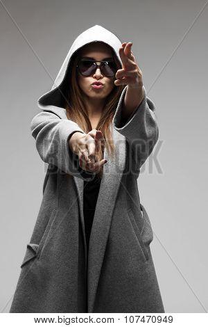 Woman in gray coat and black sunglasses posing on studio background.Beautiful fashion brunette.Styli