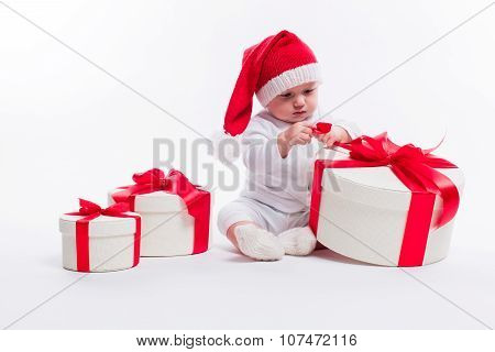 Beautiful Kid Sitting In A New Year's Cap And White Body Among Christmas Boxes With Gifts And Unpack