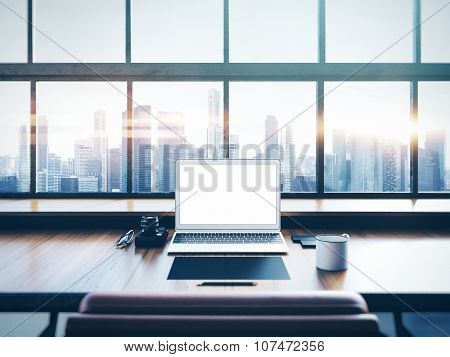 Photo of laptop on the worksplace with panoramic windows.  City at sunrise in a background. 3D rende
