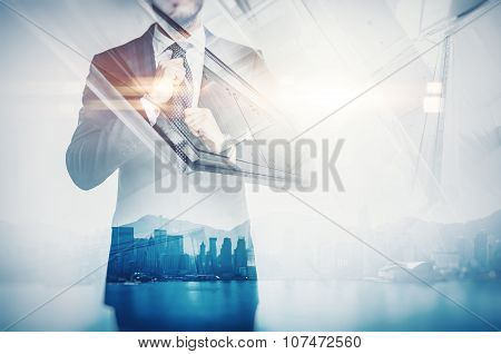 Close-up portrait of businessman straightens his own tie. Double exposure city at sunrise