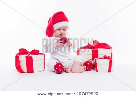 Beautiful Baby In The New Year's Cap And White Body Sits Among Boxes Of Holiday Gifts And Christmas