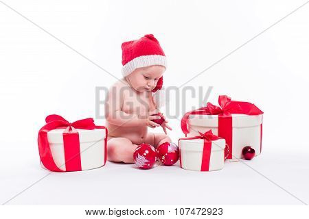 Naked Cute Baby Sitting On A White Background In A New Year's Cap Among Packaged Gifts And Christmas
