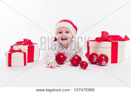 Cute Baby Lying On His Stomach In A New Year's Cap Among Christmas Balls And Red Box With Presents A