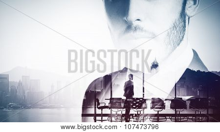 Bw close-up portrait of young businessman and meeting room on the background.