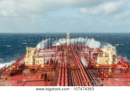 Oil tanker steering forward during stormy weather with breaking waves.
