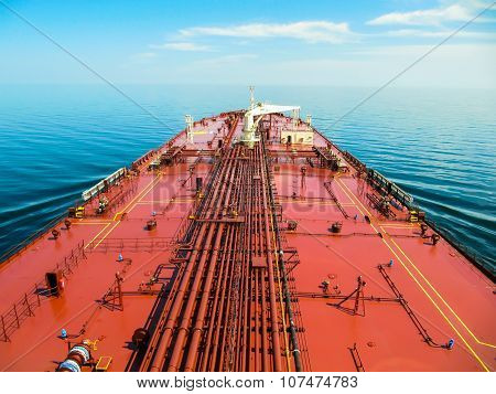 Oil tanker is proceeding in blue ocean under cloudy sky.