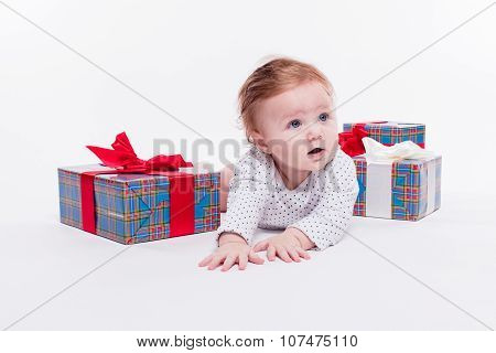 Cute Toddler Is Sitting In A New Year's Red Cap On White Background Unpacks A Gift With A Smile On H