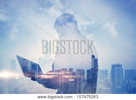 Double exposure of man with laptop and contemporary city on the background