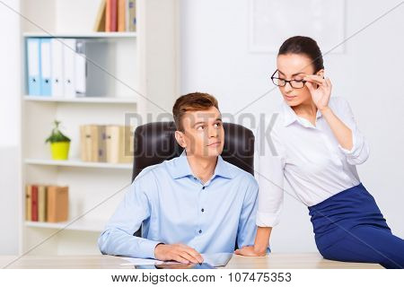 Young attractive office couple at the desk.