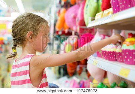 Little Girl Selecting Toy On Shelves In Supermarket.