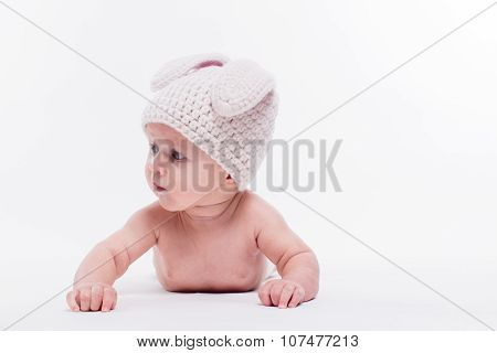 Cute Baby Girl Lying Naked On A White Background Wearing A Hat In The Form Of A Christmas Bunny With