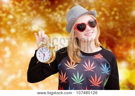 Girl in heart shaped sunglasses and hat holding alarm clock