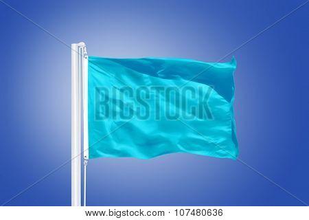 ?yan flag flying in a stiff breeze against clear blue sky.