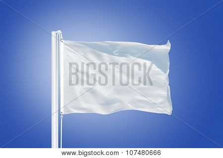 White flag flying in a stiff breeze against clear blue sky.